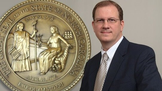 Guilford County Speeding Ticket Lawyer standing beside North Carolina State Seal